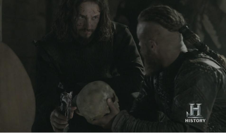 Athelstan y Ragnar, éste con los huesos del santo en la mano.